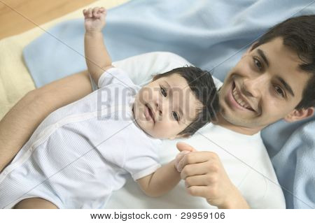 Young father and baby son posing