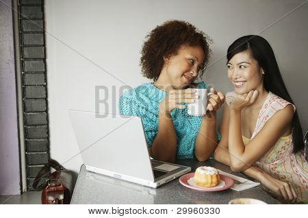 Two women with laptop and coffee and donuts