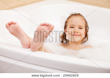 Child in the bathtub. Girl washes in the bathroom. Focus on foot
