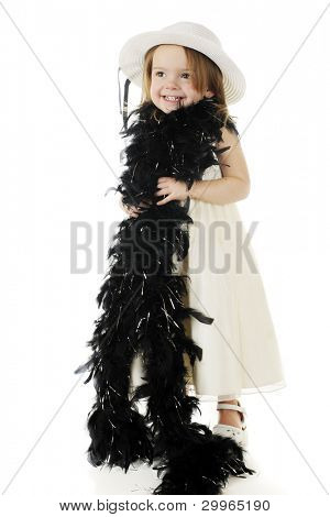 A beautiful preschooler dressed up in a white dress and hat and wrapped in a feathery black boa.  On a white background.