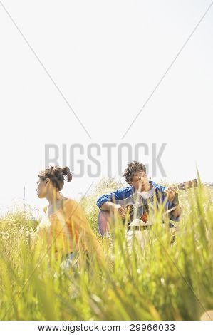 Man playing guitar in grass with girlfriend
