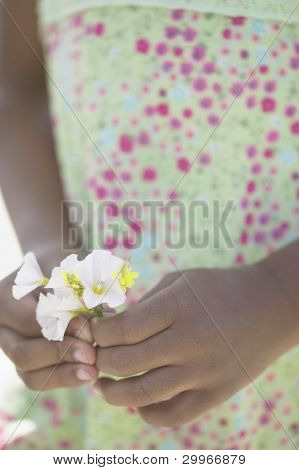 Midsection of girl holding flowers