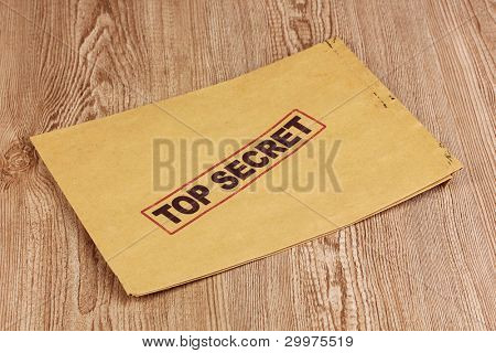 Envelope with top secret stamp on wooden background