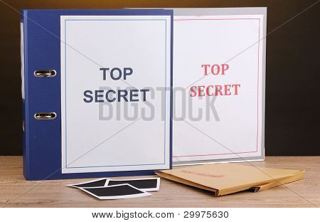 Envelopes and folders with top secret stamp and photo papers on wooden table on brown background