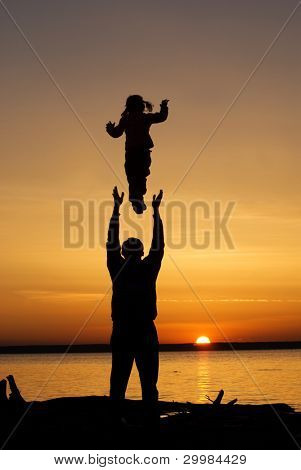 A father throws his infant child into the air