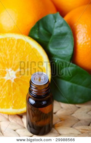 bottle of aromatic essence and some fresh oranges