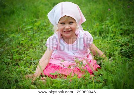 little girl sits on a summer meadow