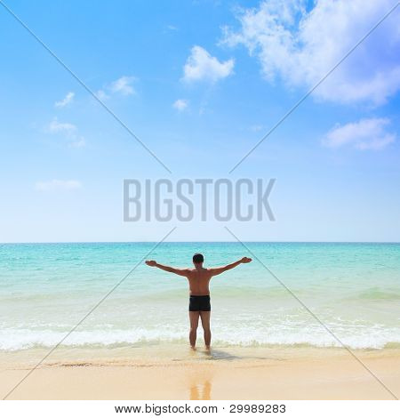 relaxed young man with his hands stretched, standing at the beach