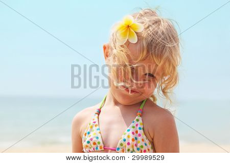 Beautiful little girl on the beach with a tropical flower plumeria