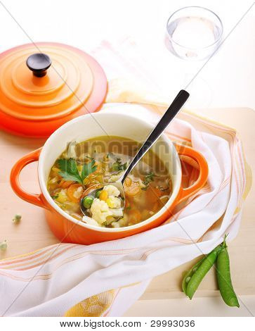 Vegetarian vegetable soup with carrots, peas and cauliflower