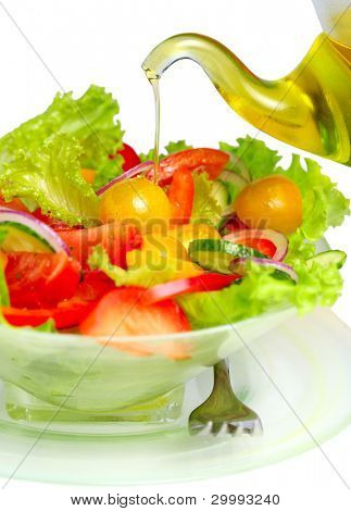 Fresh vegetable salad with olive oil pouring from bottle on white isolated background