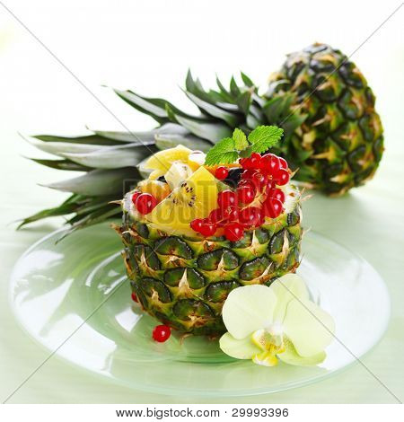 Fresh salad of tropical fruits and berries (pineapple, kiwi, peach, red currant, blueberry)