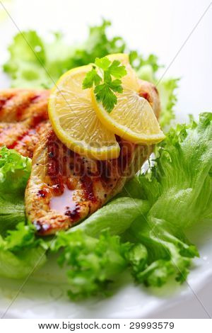 Grilled chicken breast with fresh lettuce and lemon, soft focus