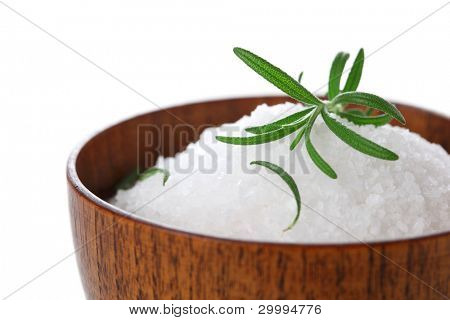 Sea salt with fresh rosemary in wooden bowl on white isolated background