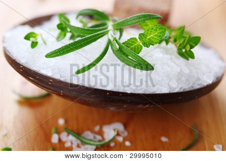 Sea salt with fresh herbs in wooden spoon closeup