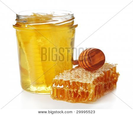 Jar of honey with honeycomb and wooden stick isolated on white background.