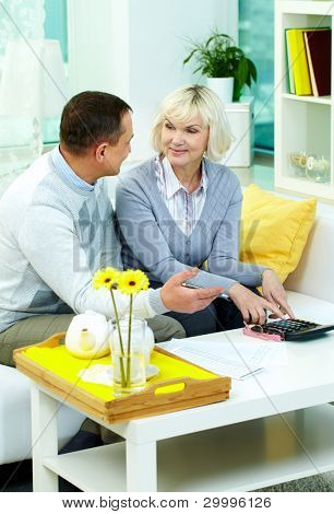 Portrait of mature man and his wife planning family budget at home
