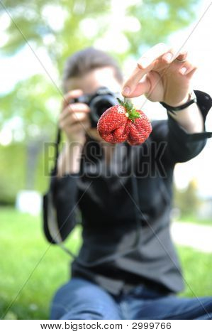 Young Girl Photographs A Berry