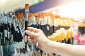 Male Artist Hand Choosing Artistic Paintbrushes. New Paint Brushes On Shelf Display In Stationery Sh poster