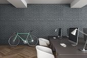 Modern Coworking Hipster Office Interior With Desktops, Computers And Bicycles On Brick Wall Backgro poster