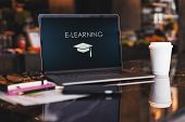 Close Up Of Laptop With Inscription On Screen E-learning And Image Of Square Academic Cap On Table I poster