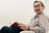 Senior Asian Man Reading Book On Chair At Home. poster