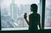Businesswoman drinking coffee at work contemplative looking out the window of high rise skyscraper b poster