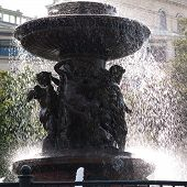 Beautiful Urban Stone Or Marble Fountain In Splashes Of Water, Giving A Cool And Coolness On A Hot S poster