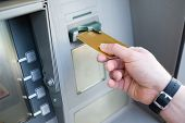 Close Up Of One Hand Inserting Atm Credit Card Into Bank Machine To Withdraw Money poster