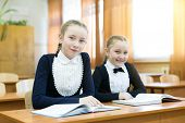 Schoolgirl Girls Write In A Notebook While Sitting At A Desk In A Classroom At School Hair Braided I poster