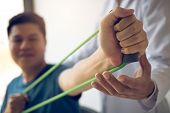 Close Up Hand Patient Doing Stretching Exercise With A Flexible Exercise Band And A Physical Therapi poster