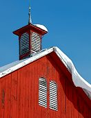 foto of louvers  - Barn roof cupola with snow drift over hanging roof and two arch topped louvered white wall vents on red painted barn - JPG