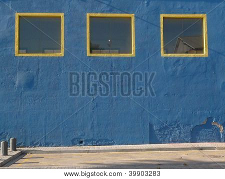 yellow framed windows on blue wall