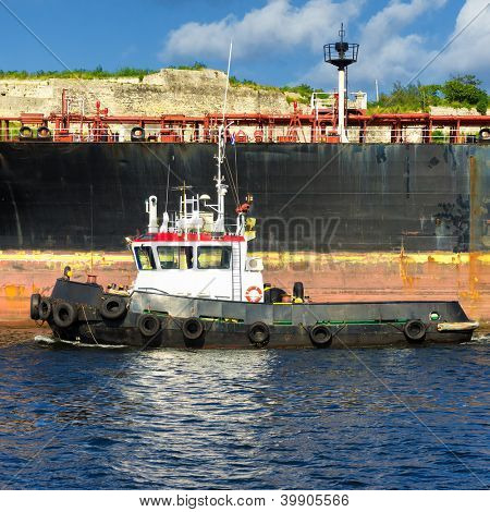 Small tugboat guiding a huge oil tanker ship