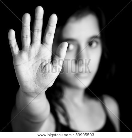 Black and white image of a girl with her hand extended signaling to stop useful to campaign against violence, gender or sexual discrimination (image focused on her hands)