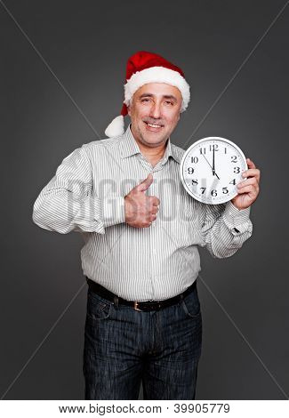 happy xmas man showing thumbs up and holding clock. studio shot over dark background