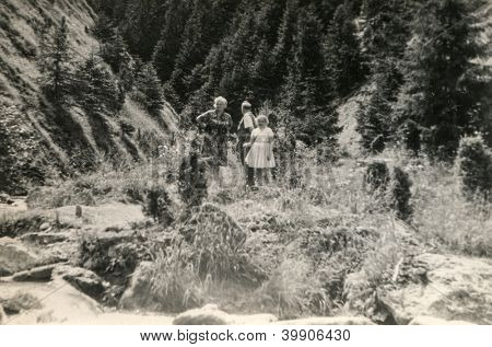 Vintage photo of family (grand father, mother and daughter) walking in mountains(sixties)