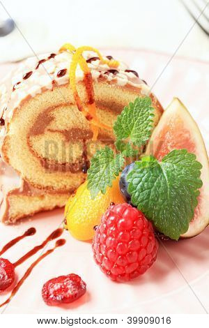 biscuit rollade filled with chocolate cream and decorated with fresh fruit