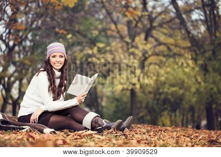 young woman reading book in autumn park