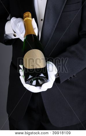Closeup of a Sommelier in a tuxedo presenting a champagne bottle, Vertical format over a light to dark gray background. Man is unrecognizable.