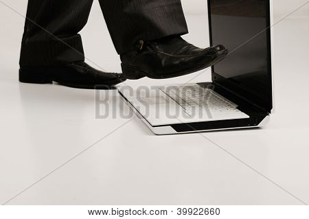 Business shoe steping and destroying laptop