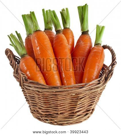 Carrot vegetables in a wooden basket isilated over white background