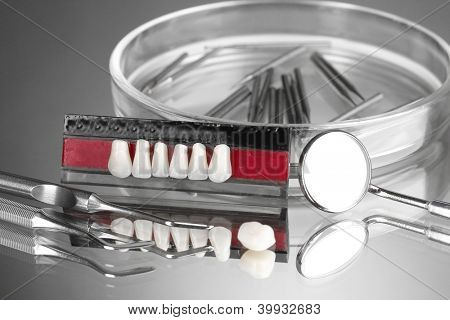 Set of dental tools with denture on grey background