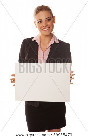 Young smiling business woman holds up a blank white card with space for your text