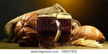 tankards of kvass and rye breads with ears, on wooden table on brown background