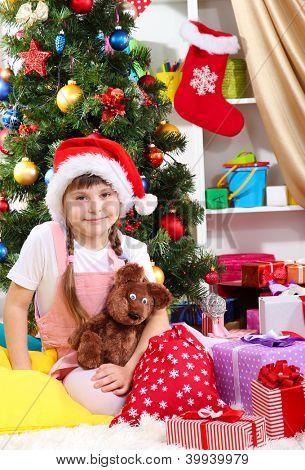 Menina de chapéu de Papai Noel perto da árvore de Natal no quarto festivamente decorado