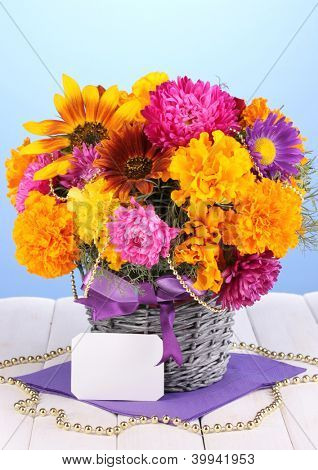 Beautiful bouquet of bright flowers with paper note on wooden table on blue background