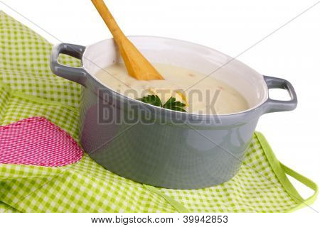 Mashed potatoes in saucepan on green pinafore isolated on white