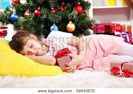 A menina adormeceu com presente em suas mãos no quarto festivamente decorado