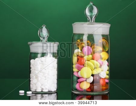 Capsules and pills in receptacles on green background